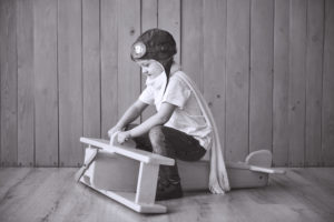 Happy kid in pilot hat playing with wooden airplane against. Childhood. Fantasy, imagination. Holiday.