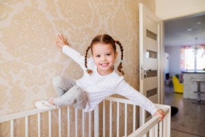 Cute little girl with braids hanging above white baby crib