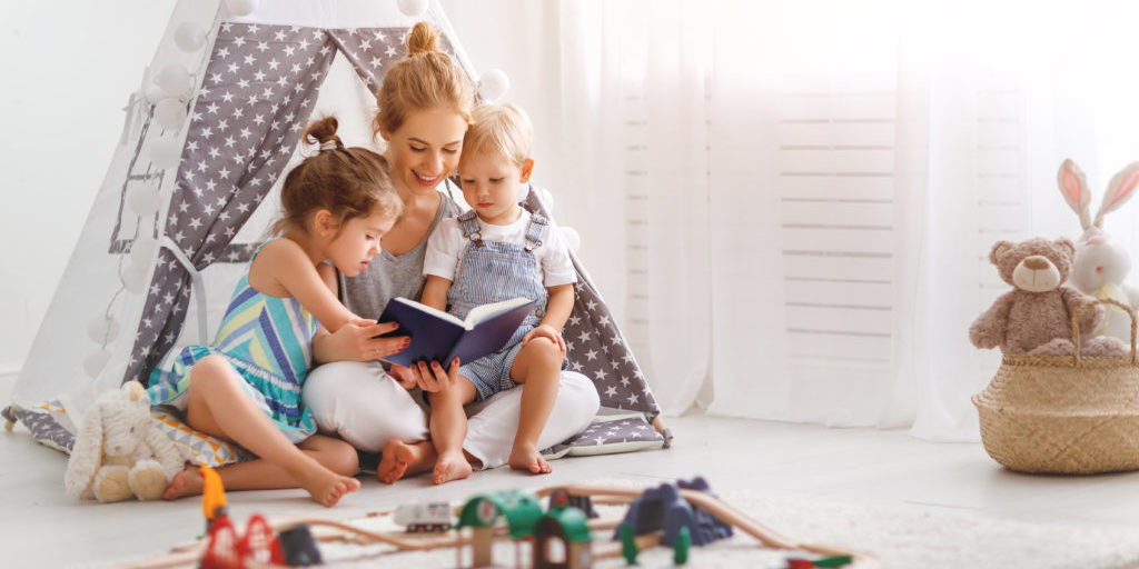 An A to Z Sleep Solution's example of a good bedtime routine. A mom reading a book to her two young children.